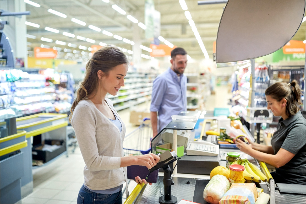 Grocery shopper swiping loyalty card at checkout register