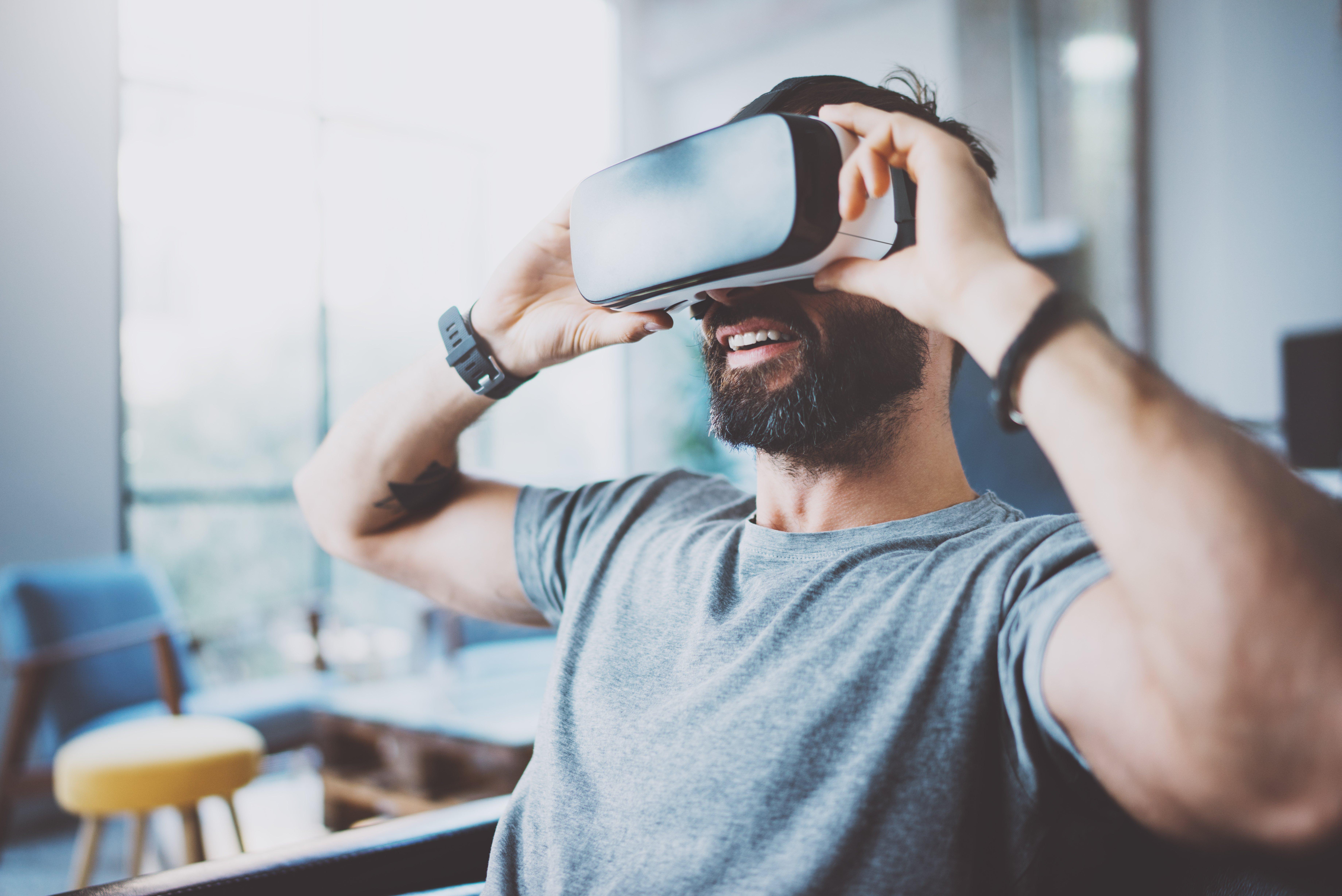 phygital reality man wearing AR virtual reality glasses at home